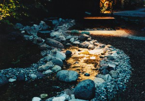 Down-lighting on creek water-feature and bench (made from salvaged iron Gothic church window frame.)