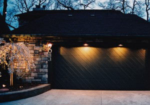 Dark garage door (part of home entrance) illuminated for safety and beauty with customized low-profile fixtures.
